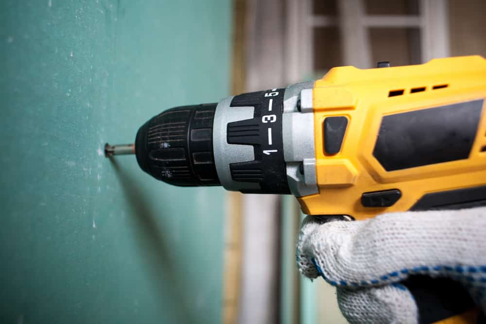 Drilling the green drywall in an unfinished basement