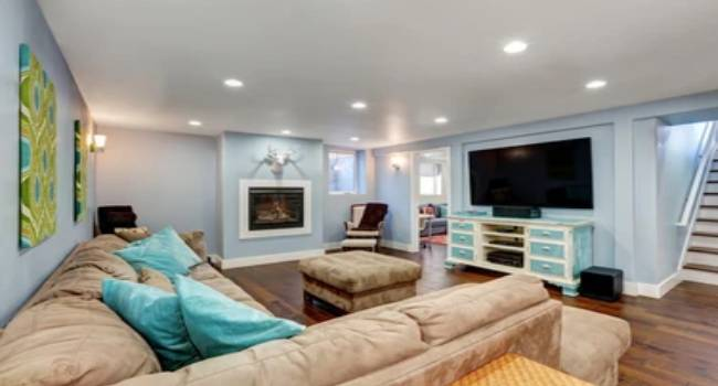 Beautiful Interior of A Living Room In The Unfinished Basement Area With Large Corner Sofa With Blue Pillows And Vintaage TV Cabinet.