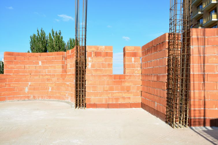Confined masonry. Load-bearing clay block wall confined at the corners with reinforced concrete tie-columns.