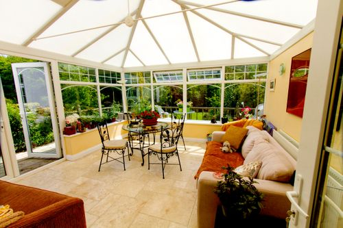 A light and airy furnished sun room (conservatory) with view of trees in the background