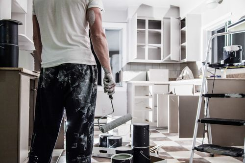 Mess of All kind of Painting Equipment in the Kitchen and Discouraged Man