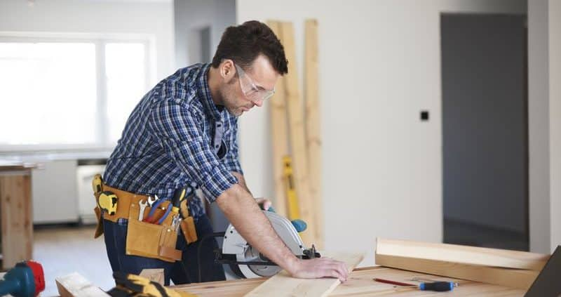 Home renovations contractor sawing board for home addition